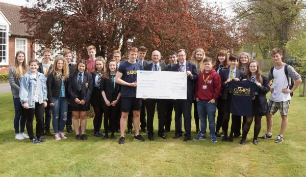 Lion Steve Sidaway presents the Peru students at Malton School with a cheque and their own digital app to record their adventures this summer
