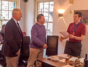 President Lion Ian welcomes Lion Russ as his sponsor - Bill Thompson - looks on