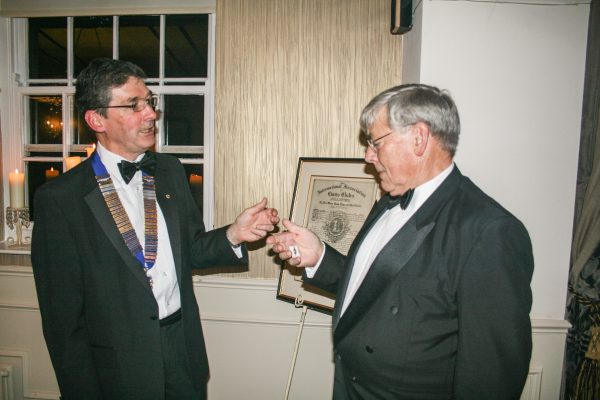 With the Club's Charter presented in 1964 in the background, President Ian presents Lion Brian Maud with his membership key that recognises Brian's sponsorship of new members over the last 12 months